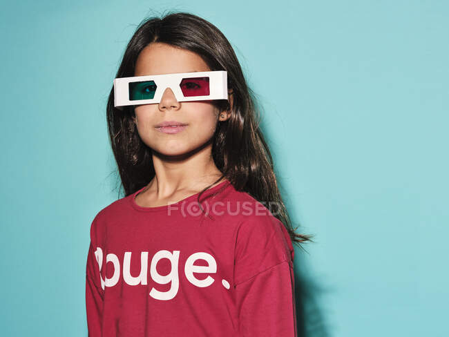 Happy preteen girl in white plastic stereoscopic glasses with red and blue lens smiling at camera while watching 3d graphic film with pleasure against turquoise background in modern studio — Stock Photo