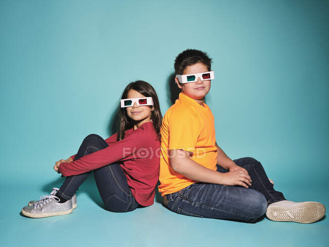 Side view of cheerful preteen boy and girl in casual clothes and three dimensional glasses looking at camera sitting back to back against blue background — Stock Photo
