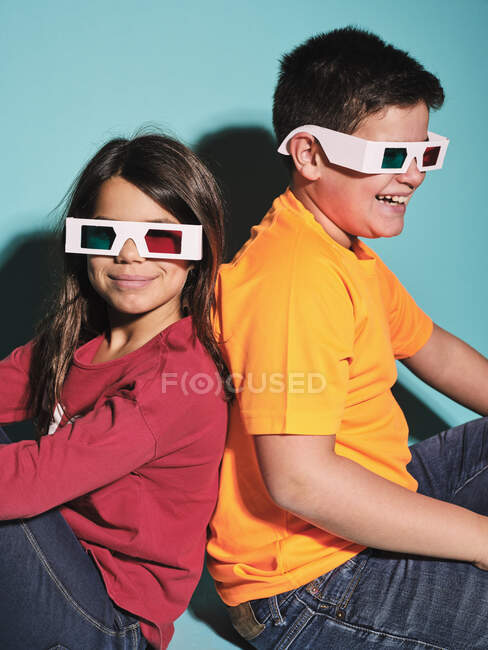 Side view of cheerful preteen boy and girl in casual clothes and three dimensional glasses sitting back to back against blue background — Stock Photo