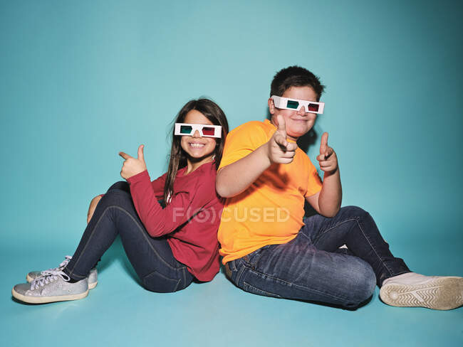 Side view of cheerful preteen boy and girl in casual clothes and three dimensional glasses pointing and looking at camera sitting back to back against blue background — Stock Photo