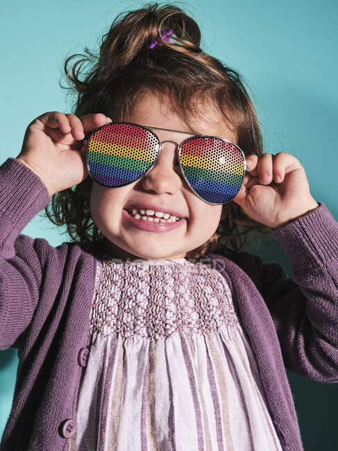 Excited small girl in rainbow sunglasses and purple casual outfit smiling at camera while standing against light blue background in contemporary studio — Stock Photo