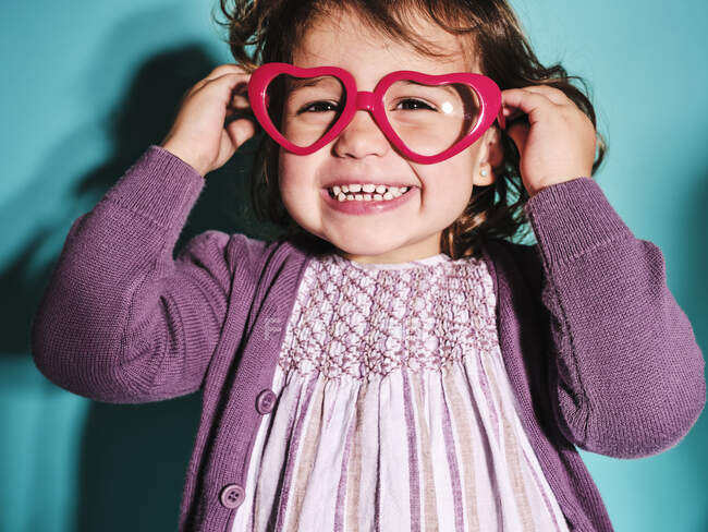 Excited small girl in heart shape eyewear glasses and purple casual outfit smiling at camera while standing against light blue background in contemporary studio — Stock Photo