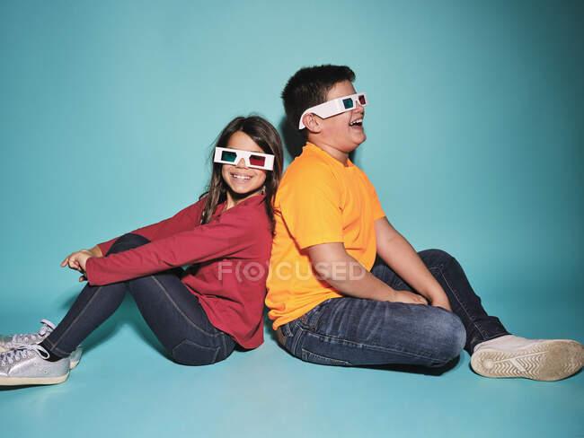 Вид сбоку веселый мальчик и девочка в повседневной одежде и трехмерные очки сидя спиной к спине на синем фоне — стоковое фото