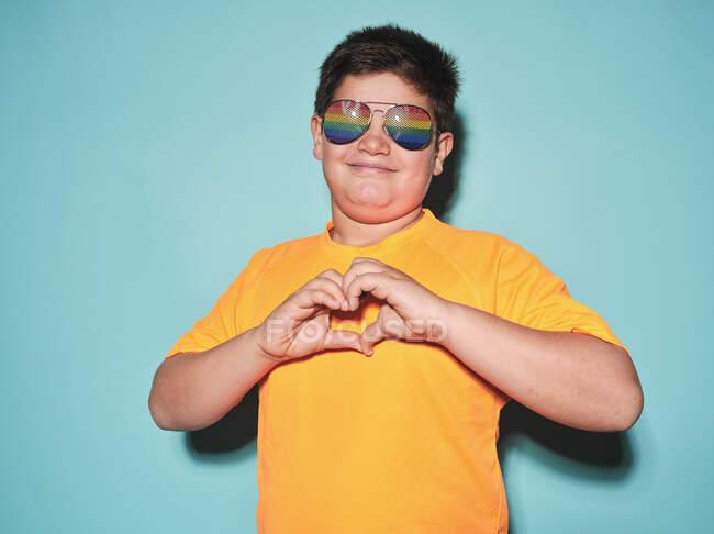 Rapaz pré-adolescente gordo positivo em camiseta amarela e óculos de sol elegantes fazendo a forma do coração com os dedos e olhando para a câmera enquanto estava de pé contra o fundo azul — Fotografia de Stock