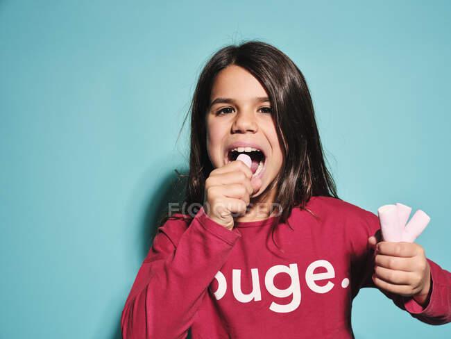 Счастливая маленькая девочка в красной повседневной одежде ест розовые мягкие конфеты зефир смотреть в камеру, стоя на синем фоне — стоковое фото