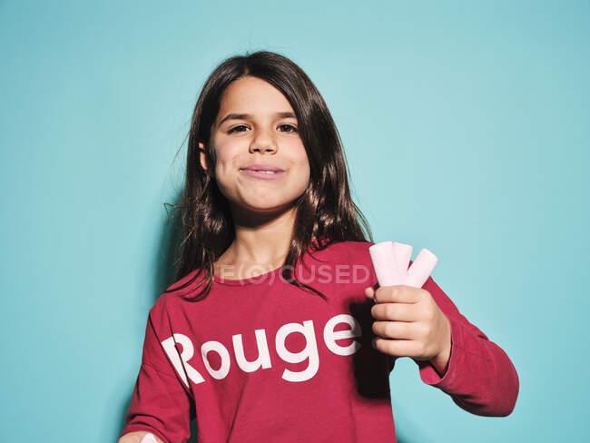 Felice bambina in rosso abbigliamento casual mangiare rosa caramelle morbide marshmallow guardando la fotocamera mentre in piedi sullo sfondo blu — Foto stock