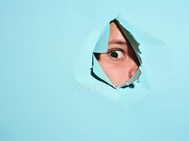 Curious kid with brown eyes looking at away through torn hole in bright blue paper in studio — Stock Photo