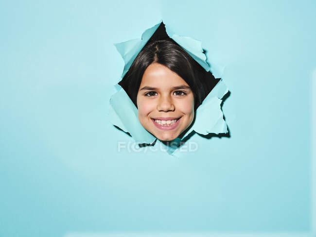 Веселая маленькая брюнетка улыбается и смотрит в камеру, выглядывая из дырки в разорванной синей бумаге. — стоковое фото