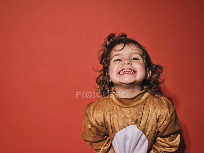 High angle of cute happy infant girl in brown animal costume laughing while standing against red background — Stock Photo