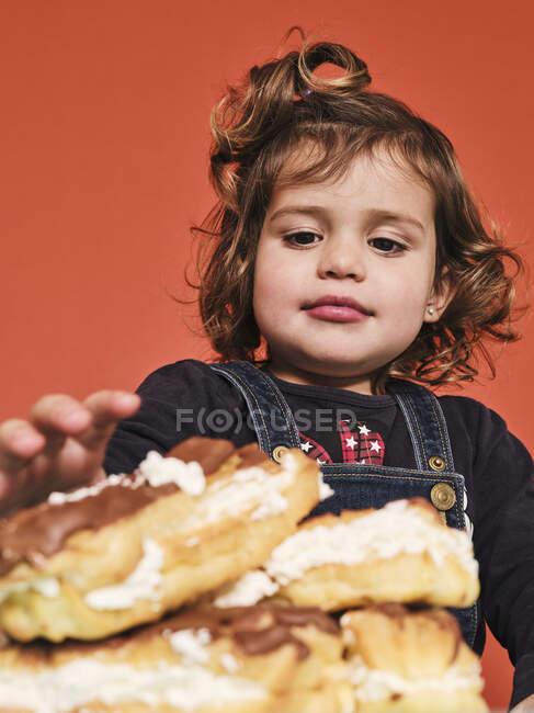Feliz niña disfrutando de dulces eclairs con chocolate mientras se sienta a la mesa sobre fondo rojo - foto de stock