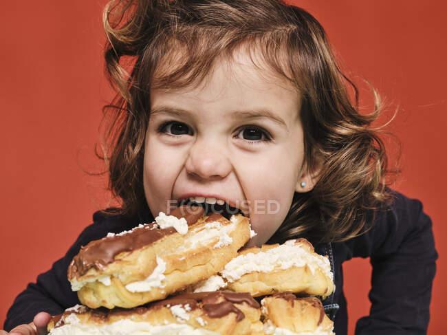Primer plano retrato de niña alegre disfrutando de dulces eclairs con chocolate mientras mira a la cámara sobre fondo rojo - foto de stock