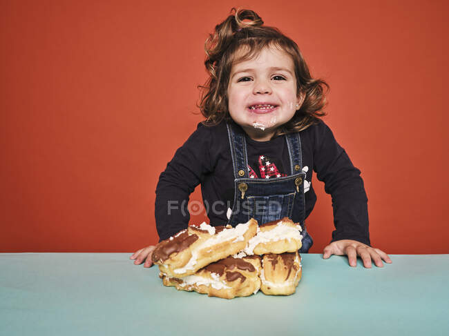 Cute little girl in casual clothes with face smeared with white cream smiling while standing at table with pile of yummy eclairs against red wall — Stock Photo