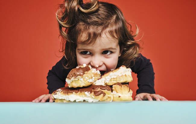 Primo piano ritratto di allegra bambina godendo dolci eclairs con cioccolato, mentre guardando lontano seduto sul tavolo sullo sfondo rosso — Foto stock