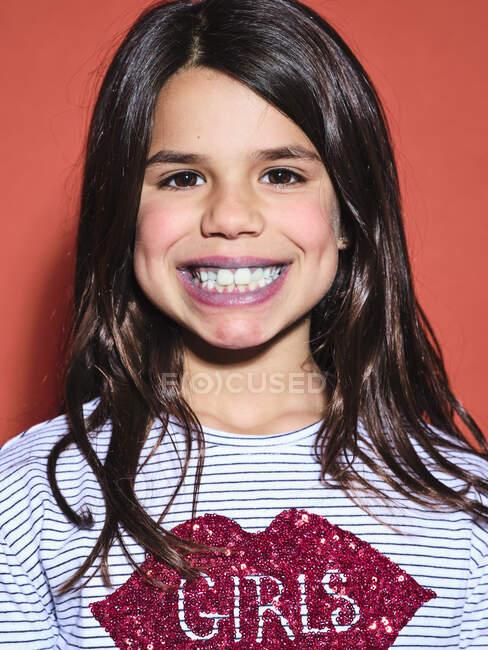 Garota pré-adolescente excitada em roupas da moda olhando para a câmera com lábios azuis depois de comer alimentos coloridos no fundo vermelho — Fotografia de Stock