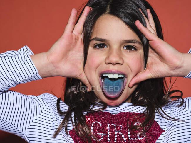 Eccitato preteen ragazza in abiti alla moda guardando la fotocamera e mostrando la lingua blu dopo aver mangiato cibo colorato su sfondo rosso — Foto stock