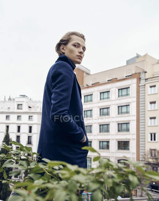 Бічний вид стильного молодого чоловіка з модним зачіскою, одягненого в елегантне пальто, що стоїть навпроти сірої кам'яної стіни міста. — стокове фото