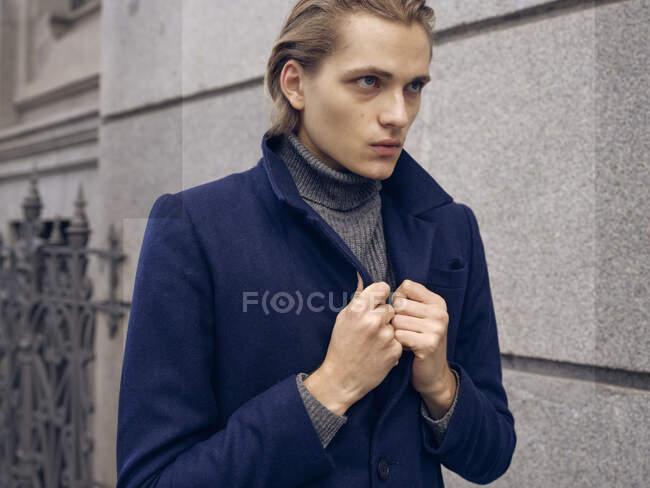 Vista laterale di elegante giovane maschio con acconciatura alla moda vestita in elegante cappotto in piedi contro il muro di pietra grigia in città — Foto stock