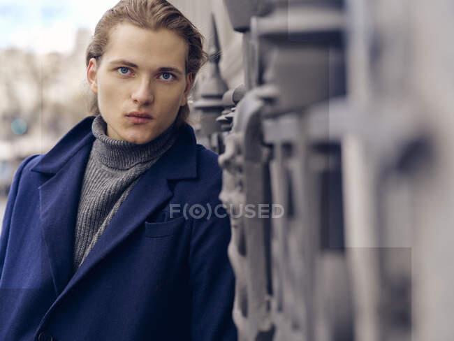 Стильний молодий чоловік з модним зачіскою, одягнений в елегантне пальто, стоїть навпроти сірої кам'яної стіни міста. — стокове фото