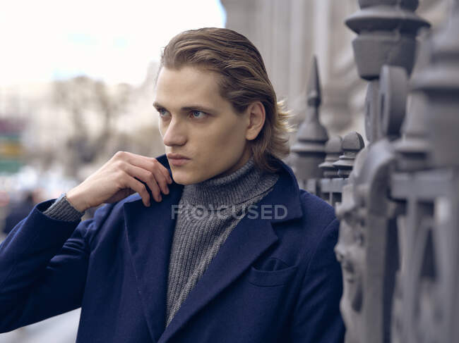 Side view of stylish young male with trendy hairstyle dressed in elegant coat standing against gray stone wall in city — Stock Photo
