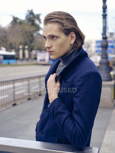 Vista lateral do jovem macho elegante com penteado na moda vestido com casaco elegante em pé contra a parede de pedra cinza na cidade — Fotografia de Stock