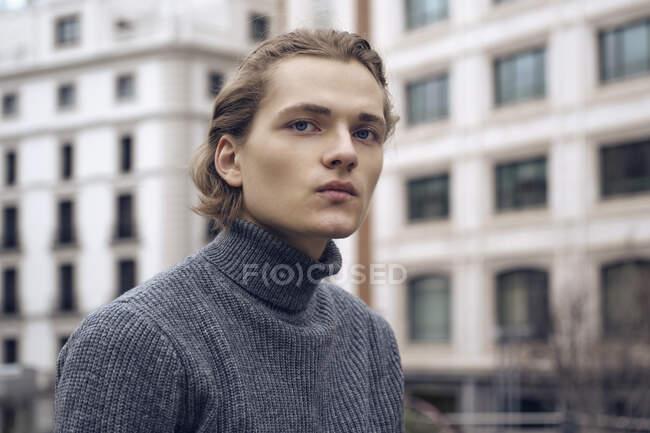 Сучасний серйозний молодий самець з стильною зачіскою в сірому теплому светрі. — стокове фото
