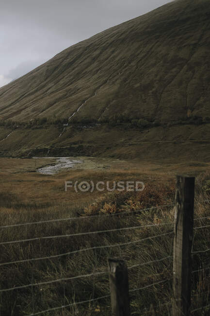 Scottish landscape with wire fence with narrow curvy river flowing among covered with grass hills under cloudy sky in autumn day — Stock Photo