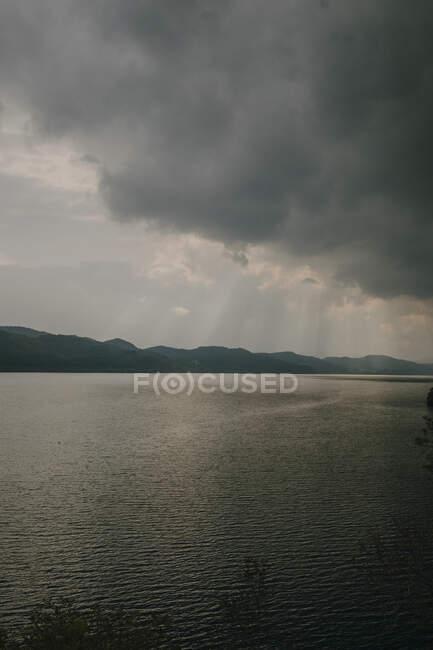 Paysage tranquille avec des rayons de soleil brillants à travers des nuages épais sur un lac calme avec de l'eau sombre — Photo de stock