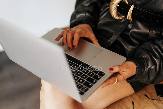 Cropped image of entrepreneur in retro outfit sitting on table and browsing laptop during work in office — Stock Photo