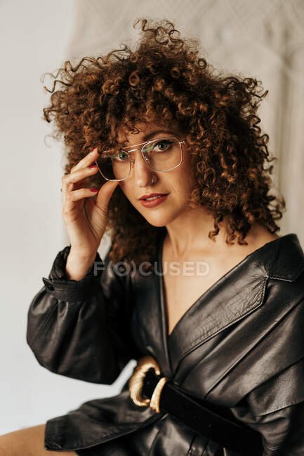 Adult businesswoman in vintage dress and with curly hair looking at camera and adjusting glasses during work — Stock Photo
