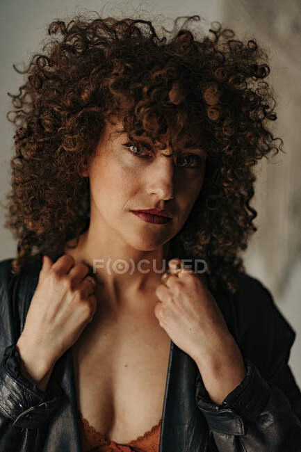 Donna sensuale in giacca di pelle e reggiseno con capelli ricci in camera — Foto stock