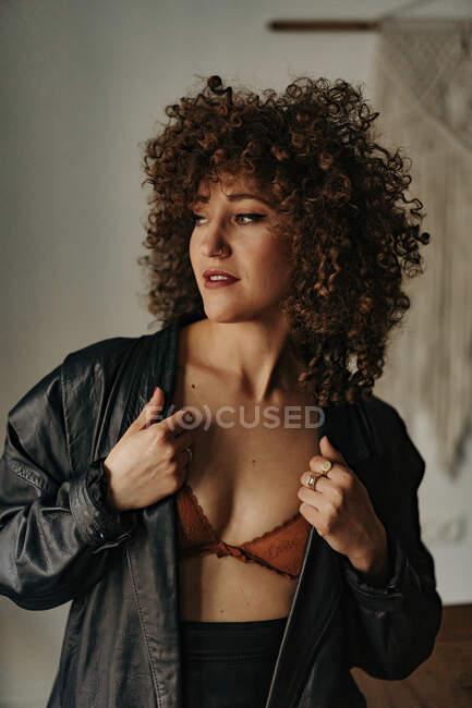 Mujer sensual en chaqueta de cuero y sujetador con pelo rizado en la habitación - foto de stock