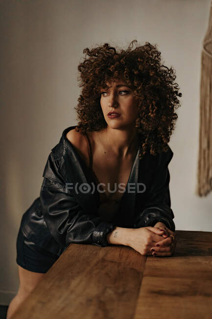 Sensual woman in leather jacket and bra with curly hair in room — Stock Photo