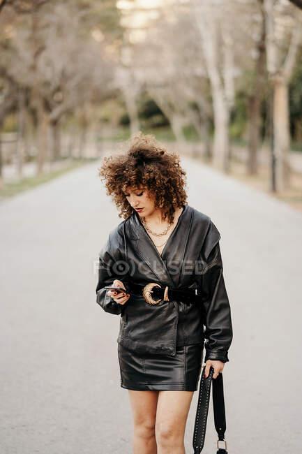 Imprenditrice donna a corpo pieno in abito vintage che cammina su asfalto — Foto stock