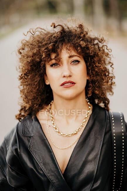 Empresária otimista em jaqueta de couro da moda e com cabelo encaracolado sorrindo para a câmera enquanto está em pé no fundo borrado da rua — Fotografia de Stock
