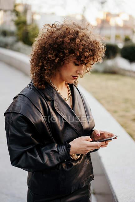 Jovem empresária em jaqueta de couro preto retro e saia navegando smartphone enquanto está em pé na passagem arqueada no parque antes do trabalho — Fotografia de Stock