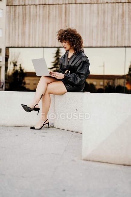 Бізнесниця в чорному шкіряному одязі сидить на кордоні і переглядає дані на ноутбуці під час роботи над віддаленим проектом на вулицях міста. — стокове фото