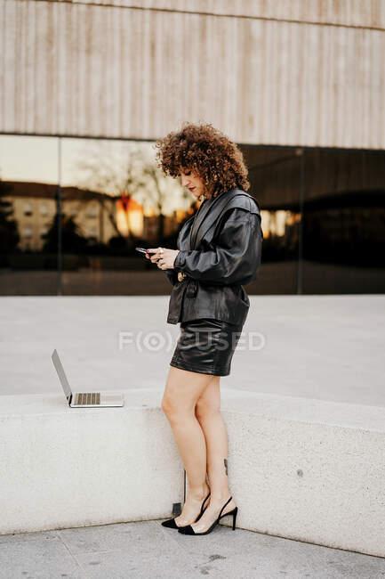Vista laterale della signora intelligente in abito vintage navigazione smartphone e in piedi vicino al confine con il computer portatile mentre si fa il lavoro remoto sulla strada — Foto stock