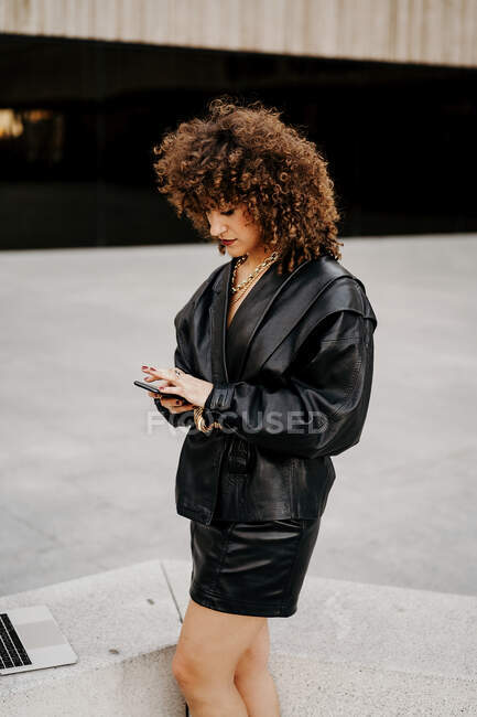 Side view of smart lady in vintage outfit browsing smartphone and standing near border with laptop while doing remote job on street — Stock Photo