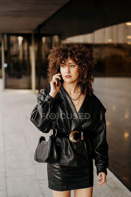 Smart businesswoman in black leather suit and with curly hair looking away and answering phone call while standing near building with glass wall on city street — Stock Photo
