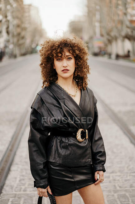 Женщина-менеджер в черном кожаном костюме юбки смотрит в сторону — стоковое фото