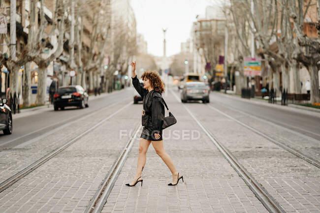 Vista lateral de la exitosa mujer de negocios en traje de cuero retro saludando la mano y tratando de coger un taxi mientras cruza los rieles del tranvía en la calle de la ciudad - foto de stock