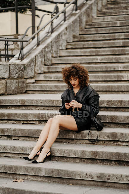 Full length slim female entrepreneur in leather skirt and jacket sitting on concrete steps and browsing smartphone on city street — Stock Photo