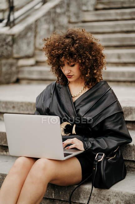 Femme d'affaires habile et bouclée portant costume en cuir noir et veste tapant sur le clavier de l'ordinateur portable tout en étant assis sur les escaliers et travaillant sur un projet à distance sur la rue de la ville — Photo de stock