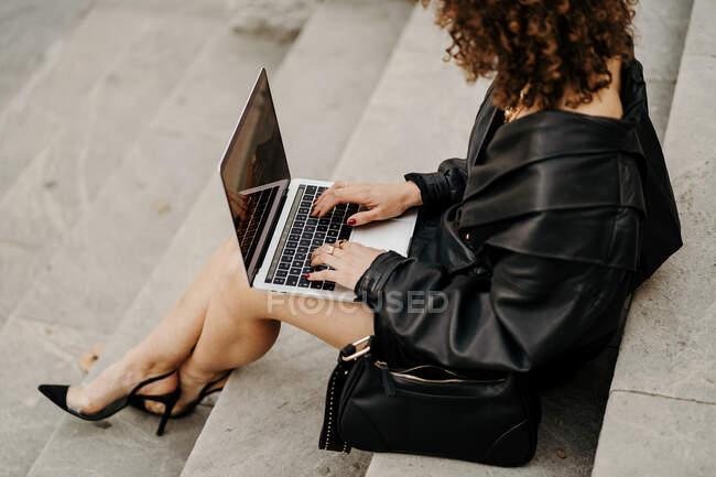 Умная кудрявая деловая женщина в черном кожаном костюме и куртке, печатающая на клавиатуре ноутбука, сидя на лестнице и работая над удаленным проектом на городской улице — стоковое фото