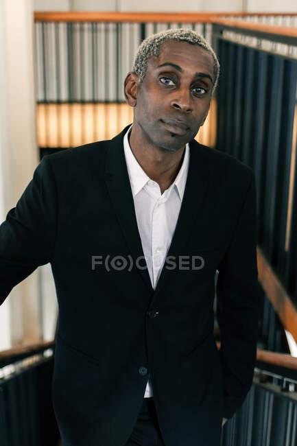Confiado hombre de negocios negro apoyado en barandilla - foto de stock
