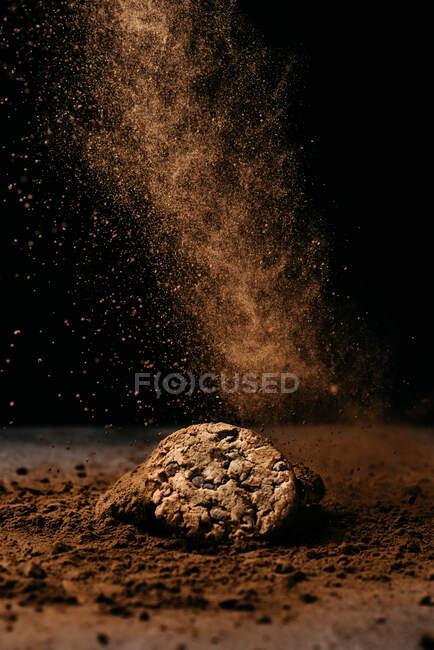 Одяг смачного вівсяного печива з шоколадними фігурками на столі, вкритий порошком какао з летючим порошком на чорному тлі. — стокове фото