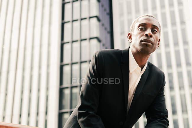 Впевнений чорний бізнесмен покладається на поручні — стокове фото