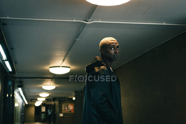 Side view of adult black guy in outerwear looking away while standing in dark underground passage in city — Stock Photo