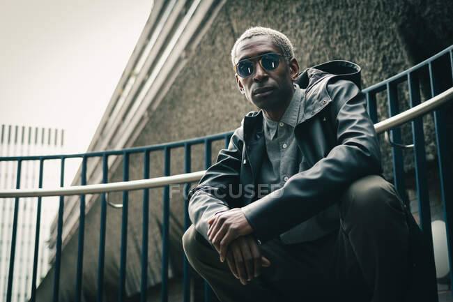 Stylish black man sitting on haunches on street — Stock Photo