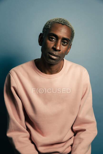 Взрослый афроамериканец в модной розовой толстовке, смотрящий в камеру на синем фоне — стоковое фото